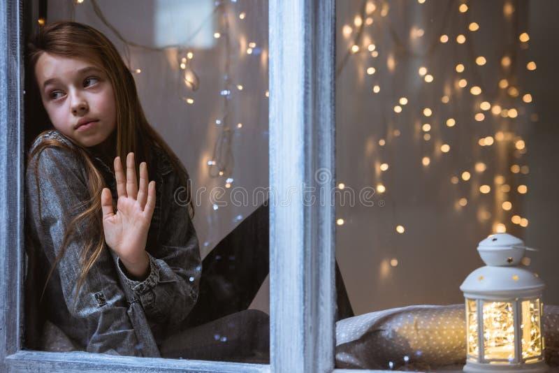 Παιδί που φαίνεται έξω το παράθυρο στοκ εικόνα