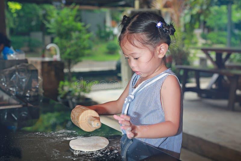 Παιδί που χρησιμοποιεί την ξύλινη κυλώντας καρφίτσα στη ζύμη στοκ φωτογραφία με δικαίωμα ελεύθερης χρήσης