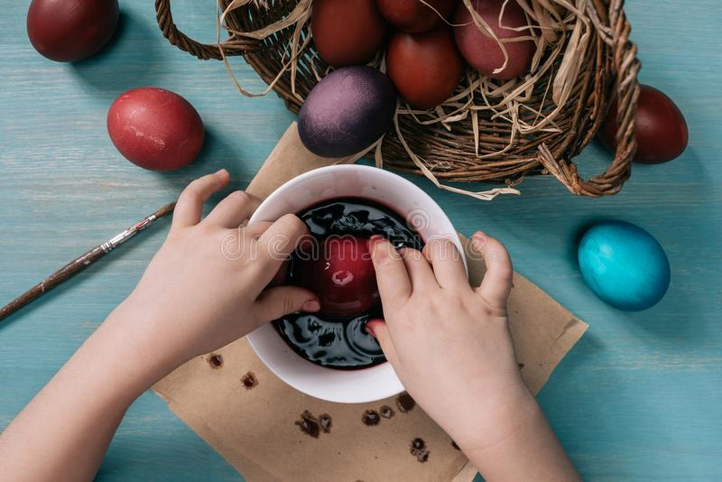Παιδί που χρωματίζει τα αυγά Πάσχας στο φλυτζάνι με το χρώμα στο σπίτι στοκ φωτογραφία με δικαίωμα ελεύθερης χρήσης
