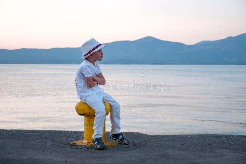 Παιδί στα άσπρα ενδύματα που κάθεται από τον ωκεανό, θάλασσα με τα βουνά στο υπόβαθρο Κάθισμα και αναμονή seascape και στοκ φωτογραφία με δικαίωμα ελεύθερης χρήσης