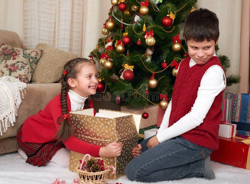 Παιδί στο καπέλο santa που έχει τη διασκέδαση και το παιχνίδι, που μοιράζονται τα δώρα, διακόσμηση Χριστουγέννων στο σπίτι, ευτυχ στοκ εικόνα με δικαίωμα ελεύθερης χρήσης