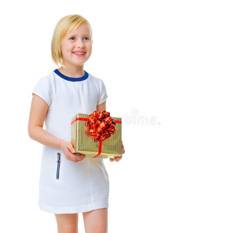 Παιδί στο λευκό με το κιβώτιο χριστουγεννιάτικου δώρου που κοιτάζει στο διάστημα αντιγράφων στοκ φωτογραφία