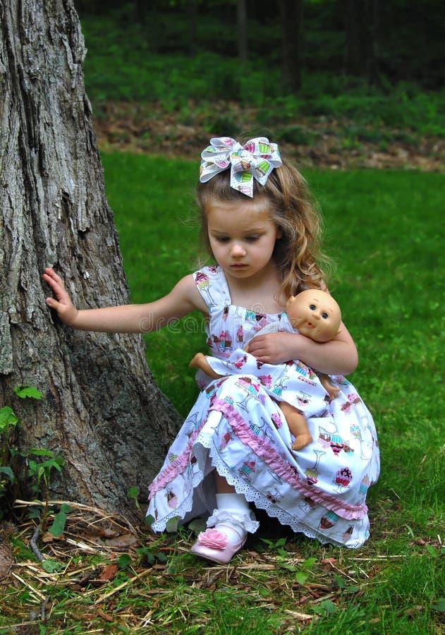 Παιδί υπαίθρια με την κούκλα της στοκ εικόνες