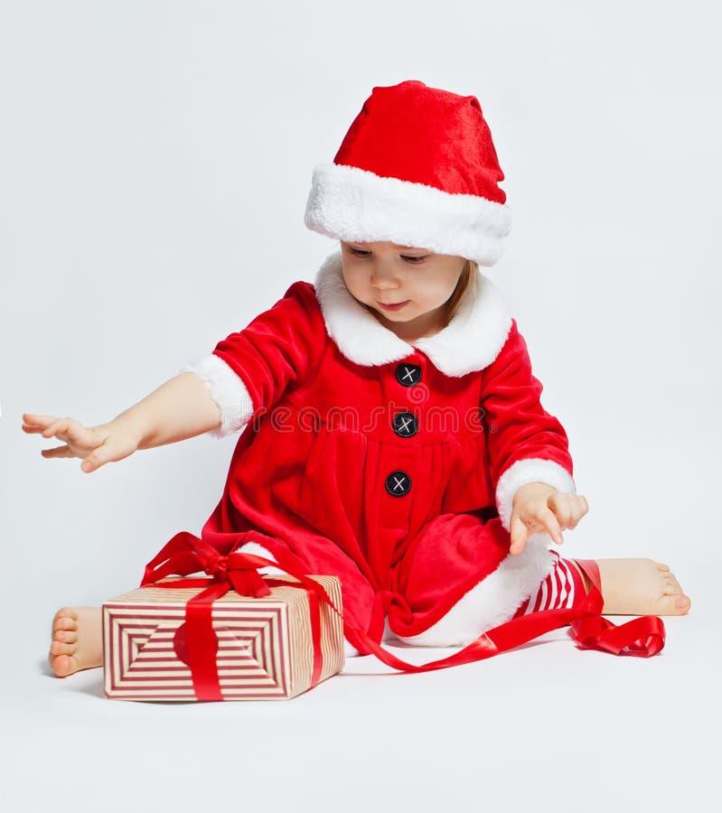 Παιδί Χριστουγέννων στο κιβώτιο δώρων Χριστουγέννων ανοίγματος καπέλων Santa στοκ εικόνες