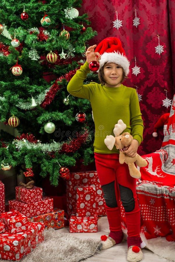 Παιδί Χριστουγέννων Cherful που παρουσιάζει μπιχλιμπίδι στοκ φωτογραφία με δικαίωμα ελεύθερης χρήσης
