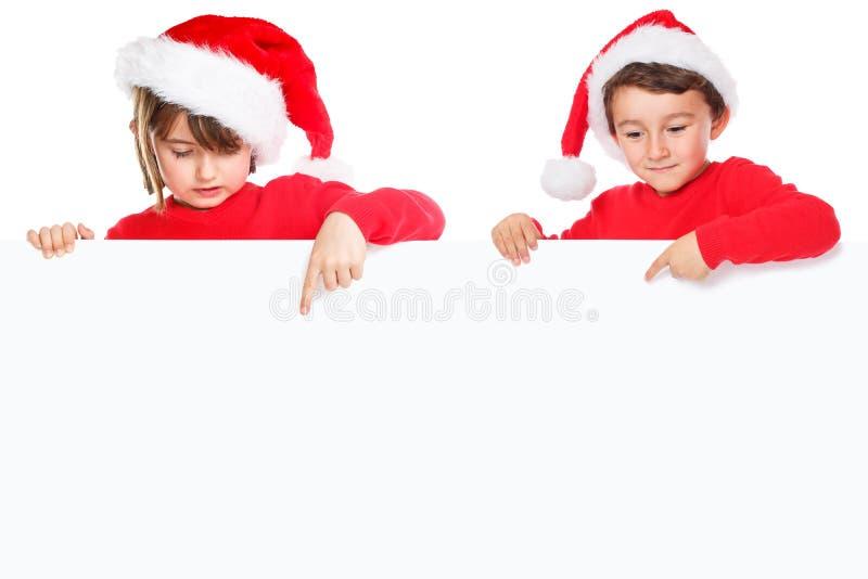 Παιδιά Άγιος Βασίλης παιδιών Χριστουγέννων που δείχνουν το κενό έμβλημα copysp στοκ φωτογραφία με δικαίωμα ελεύθερης χρήσης