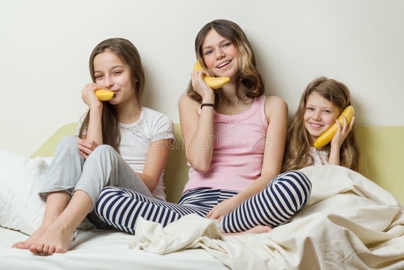 Παιδιά αδελφών στο παιχνίδι πυτζαμών το πρωί στο κρεβάτι Κρατήστε τις μπανάνες ως τηλέφωνα που μιλούν και που γελούν στοκ εικόνα με δικαίωμα ελεύθερης χρήσης