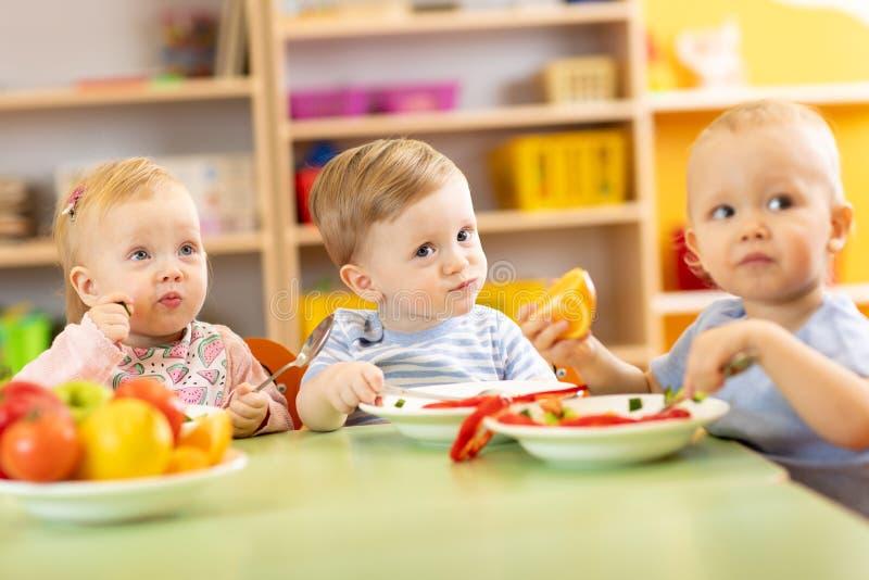 Παιδιά βρεφικών σταθμών που έχουν το γεύμα στη φύλαξη στοκ φωτογραφίες