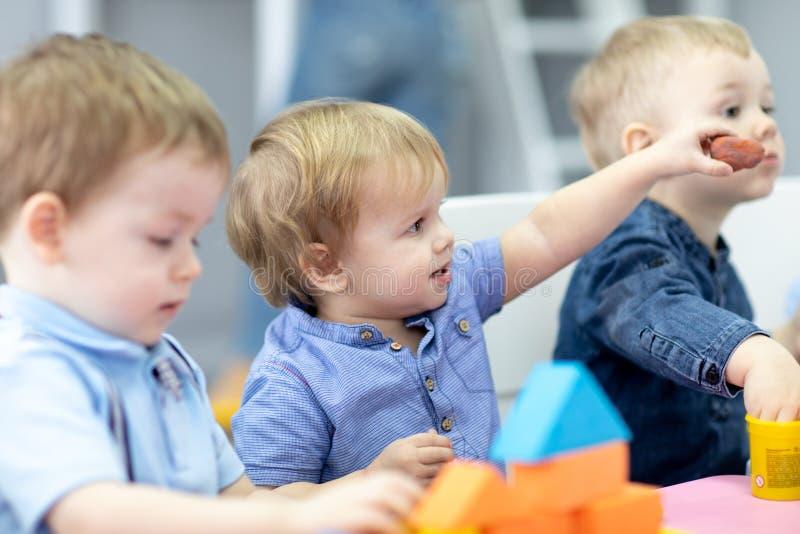 Παιδιά βρεφικών σταθμών στο μάθημα στον παιδικό σταθμό στοκ εικόνες