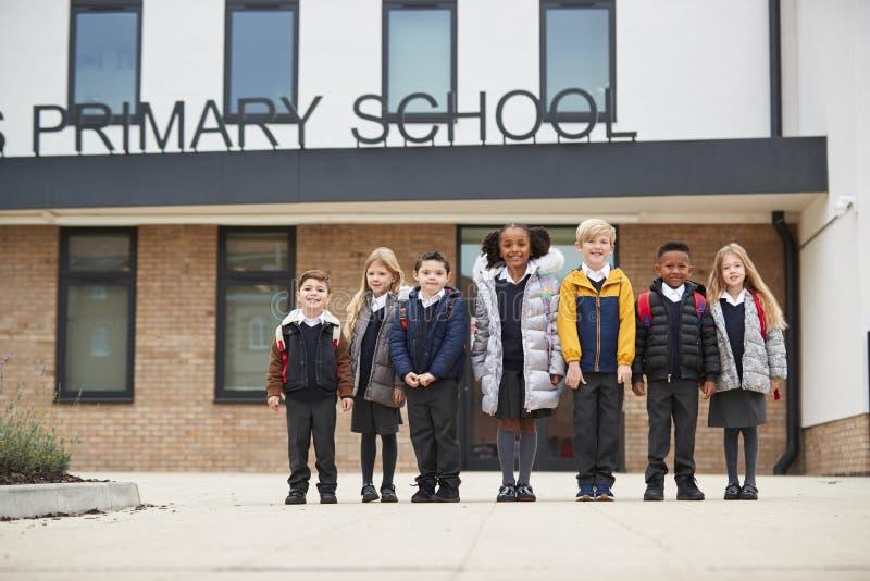 Παιδιά δημοτικού σχολείου που στέκονται μπροστά από το σχολείο τους που κοιτάζει στη κάμερα, πλήρες μήκος, χαμηλή γωνία στοκ φωτογραφίες