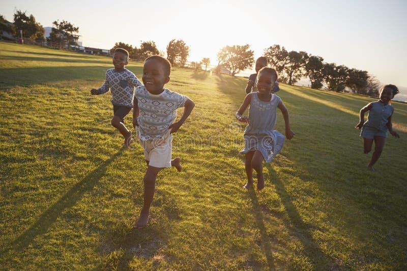 Παιδιά δημοτικών σχολείων που τρέχουν στη κάμερα σε έναν ανοικτό τομέα στοκ εικόνες