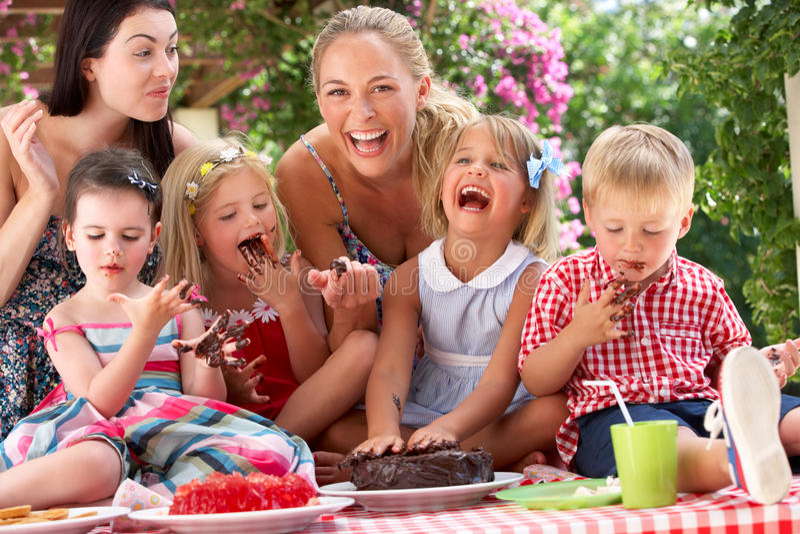 Παιδιά και μητέρες που τρώνε το κέικ σε Outd στοκ εικόνα με δικαίωμα ελεύθερης χρήσης