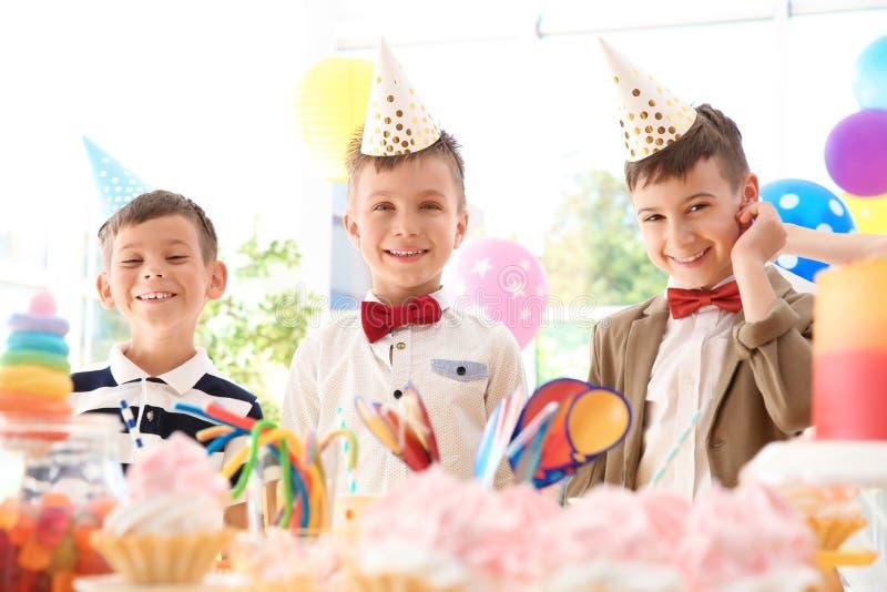 Παιδιά κοντά στον πίνακα με τις απολαύσεις στη γιορτή γενεθλίων στο εσωτερικό στοκ εικόνες με δικαίωμα ελεύθερης χρήσης