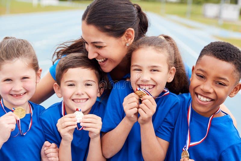 Παιδιά Με Γυναικείο Προπονητή Που Δείχνουν Νικητές Μετάλλια Την Ημέρα Του Αθλητισμού στοκ εικόνες