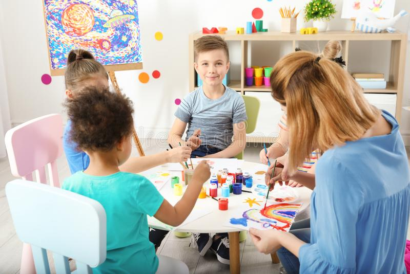 Παιδιά με το θηλυκό δάσκαλο στο μάθημα ζωγραφικής στοκ φωτογραφίες