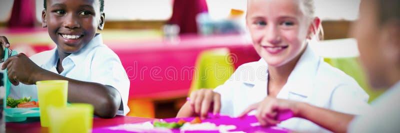 Παιδιά που έχουν το μεσημεριανό γεύμα κατά τη διάρκεια του χρόνου σπασιμάτων στη σχολική καφετέρια στοκ εικόνες