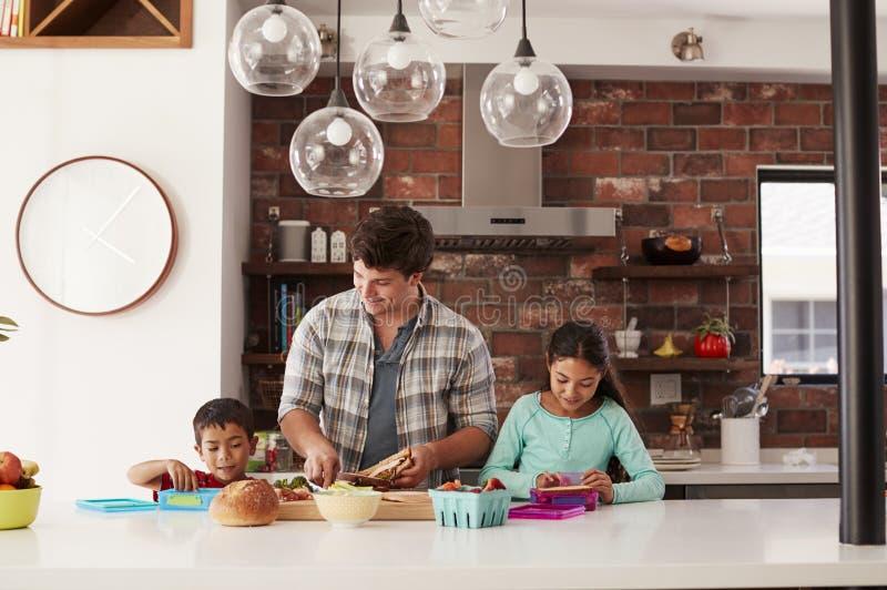 Παιδιά που βοηθούν τον πατέρα για να κάνει τα σχολικά μεσημεριανά γεύματα στην κουζίνα στο σπίτι στοκ φωτογραφίες