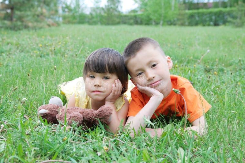 Παιδιά που βρίσκονται στη χλόη στο πάρκο που έχει τη διασκέδαση Το μικρό κορίτσι και το αγόρι χαλαρώνουν με το χαμόγελο στοκ εικόνα