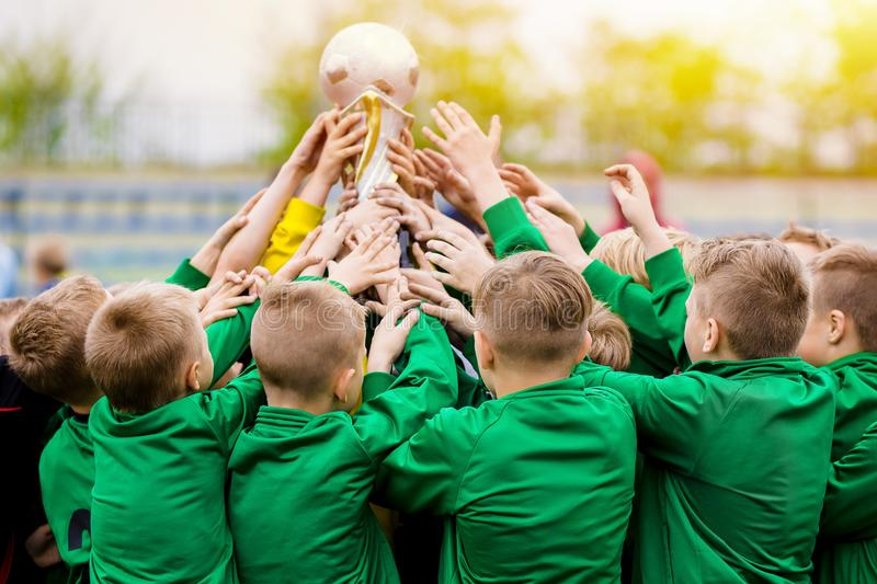 Παιδιά που γιορτάζουν τη νίκη ποδοσφαίρου Νέο τρόπαιο εκμετάλλευσης ποδοσφαιριστών στοκ φωτογραφία με δικαίωμα ελεύθερης χρήσης