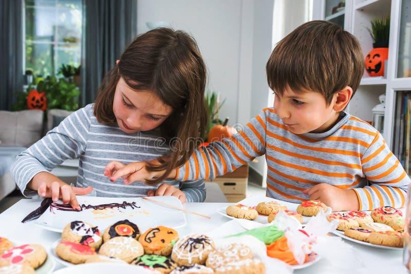 Παιδιά που διακοσμούν τα μπισκότα για αποκριές στοκ εικόνα