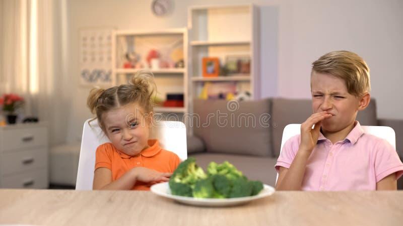 Παιδιά που εξετάζουν με την αποστροφή το μπρόκολο, unappetizing γεύμα, tasteless υγιή τρόφιμα στοκ εικόνες
