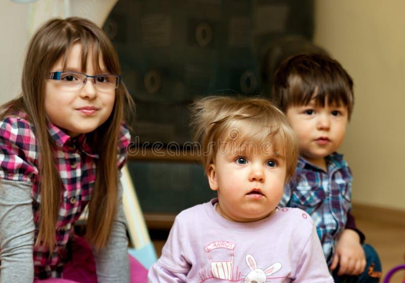 παιδιά που κάθονται από κ&omicron στοκ εικόνα