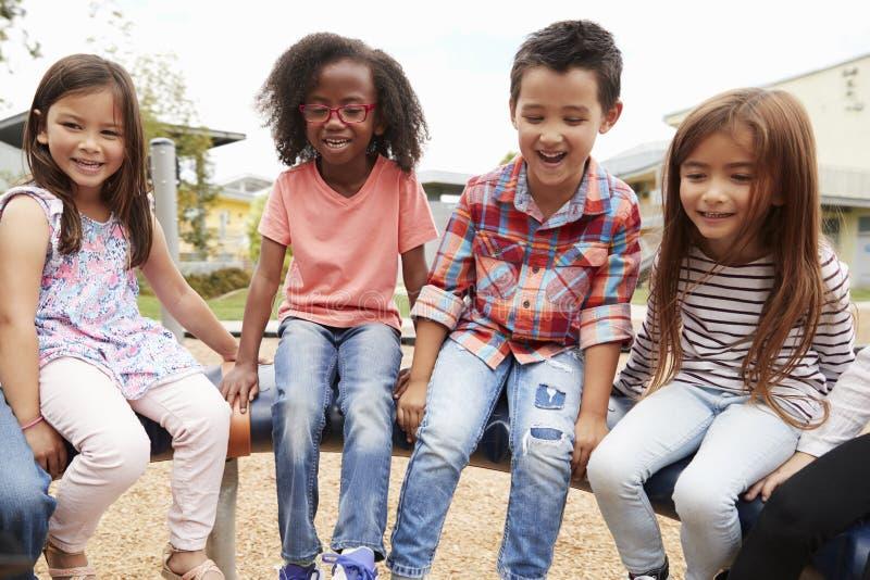 Παιδιά που κάθονται σε ένα περιστρεφόμενο ιπποδρόμιο schoolyard τους στοκ φωτογραφία με δικαίωμα ελεύθερης χρήσης
