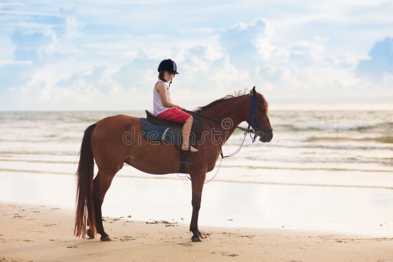 Παιδιά που οδηγούν το άλογο στην παραλία Τα παιδιά οδηγούν τα άλογα στοκ φωτογραφία με δικαίωμα ελεύθερης χρήσης