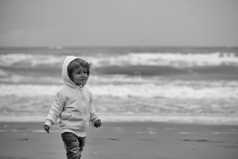Παιδιά που παίζουν - ευτυχές παιχνίδι Αγοράκι στο με κουκούλα παλτό στοκ εικόνες