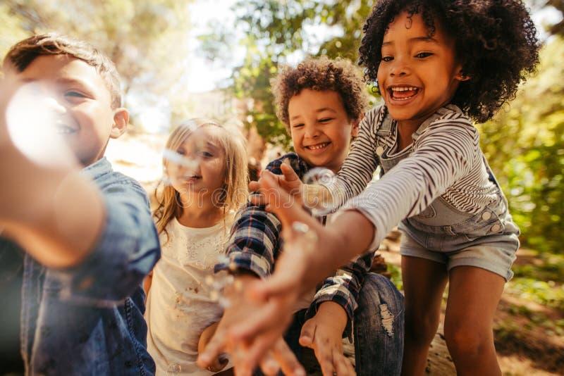 Παιδιά που παίζουν με τις φυσαλίδες σαπουνιών στοκ εικόνες