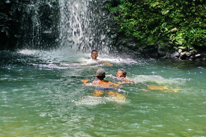 Παιδιά που παίζουν σε μια λίμνη στη βάση ενός καταρράκτη στον Ισημερινό στοκ φωτογραφία με δικαίωμα ελεύθερης χρήσης