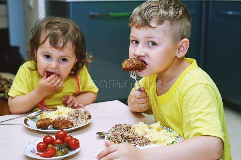 Παιδιά που τρώνε στο σπίτι τα σπιτικά τρόφιμα στοκ εικόνα
