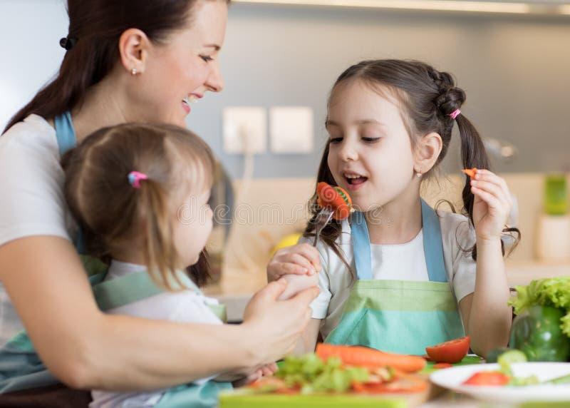 Παιδιά που τρώνε φαγητό κατά τη διάρκεια του μαγειρέματος με τη μητέρα τους στοκ εικόνες με δικαίωμα ελεύθερης χρήσης