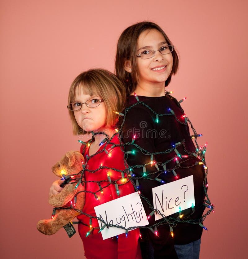 Παιδιά που τυλίγονται επάνω στα φω'τα Χριστουγέννων για τις διακοπές άτακτες και στοκ εικόνα με δικαίωμα ελεύθερης χρήσης