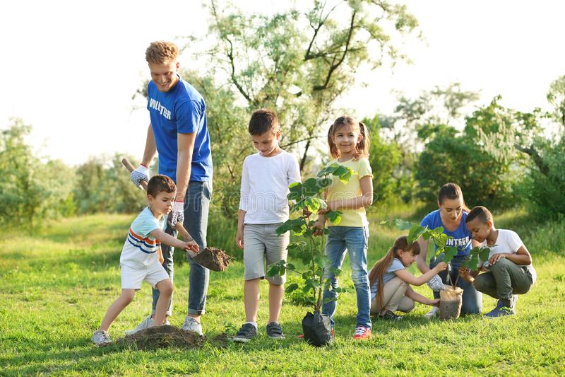 Παιδιά που φυτεύουν τα δέντρα με τους εθελοντές στοκ φωτογραφίες