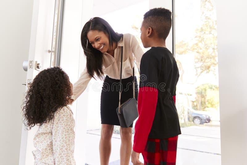Παιδιά που χαιρετούν και που αγκαλιάζουν την εργαζόμενη μητέρα επιχειρηματιών δεδομένου ότι επιστρέφει το σπίτι από την εργασία στοκ εικόνα με δικαίωμα ελεύθερης χρήσης