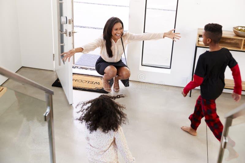 Παιδιά που χαιρετούν και που αγκαλιάζουν την εργαζόμενη μητέρα επιχειρηματιών δεδομένου ότι επιστρέφει το σπίτι από την εργασία στοκ εικόνες