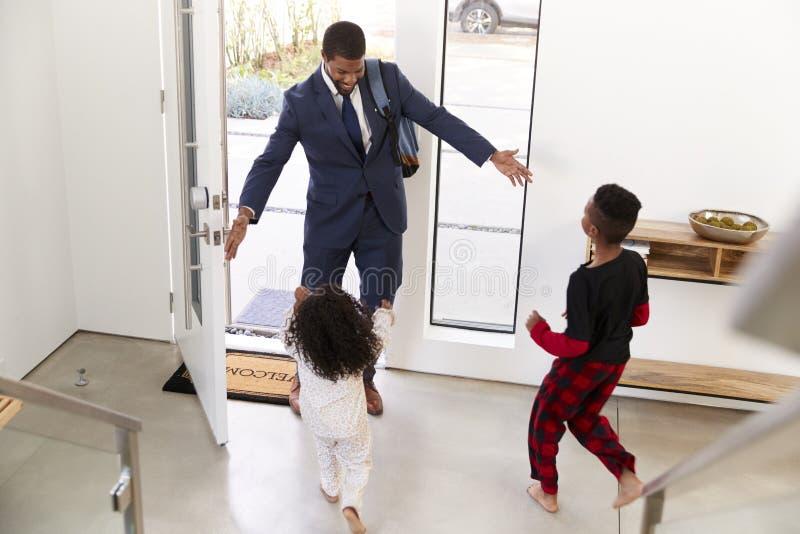 Παιδιά που χαιρετούν και που αγκαλιάζουν τον εργαζόμενο πατέρα επιχειρηματιών δεδομένου ότι επιστρέφει το σπίτι από την εργασία στοκ φωτογραφία με δικαίωμα ελεύθερης χρήσης