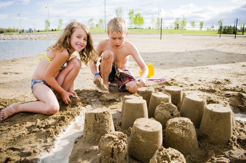 Παιδιά σε μια παραλία με το κάστρο άμμου στοκ εικόνα