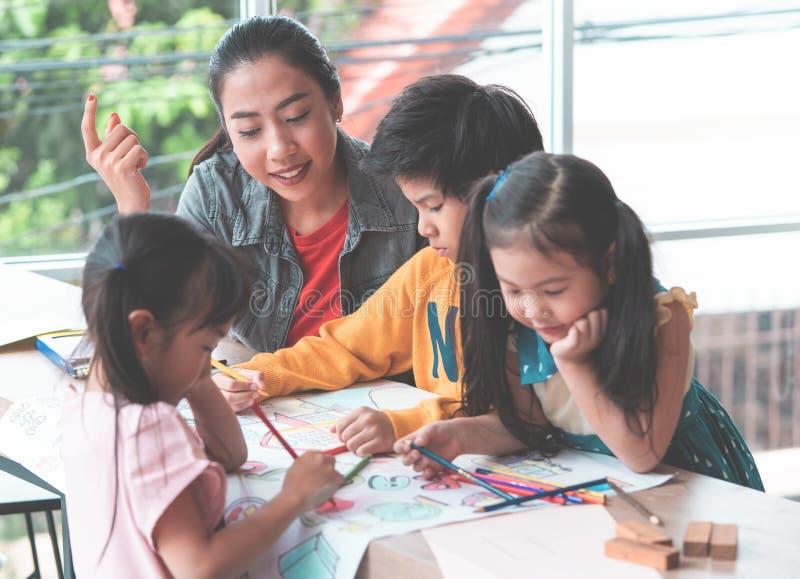 Παιδιά σπουδαστών που χρωματίζουν σε χαρτί στην ομάδα τέχνης στοκ εικόνα