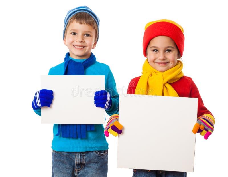 Παιδιά στα χειμερινά ενδύματα με τα κενά εμβλήματα κενών στοκ φωτογραφίες
