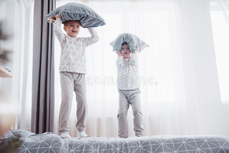 Παιδιά στις μαλακές θερμές πυτζάμες που παίζουν στο κρεβάτι στοκ φωτογραφία