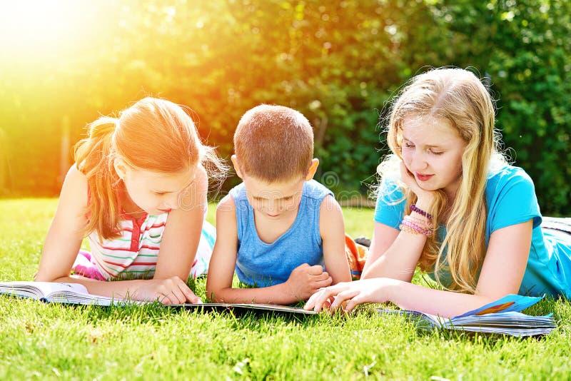Παιδιά φίλων που διαβάζουν το outdoori βιβλίων στη χλόη στοκ εικόνες