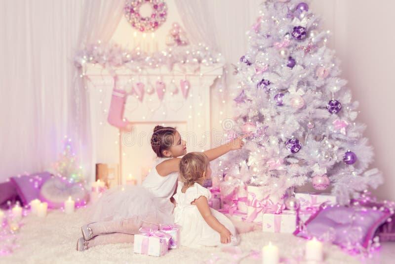 Παιδιά Χριστουγέννων που διακοσμούν το χριστουγεννιάτικο δέντρο, παιδί και κοριτσάκια στοκ εικόνα