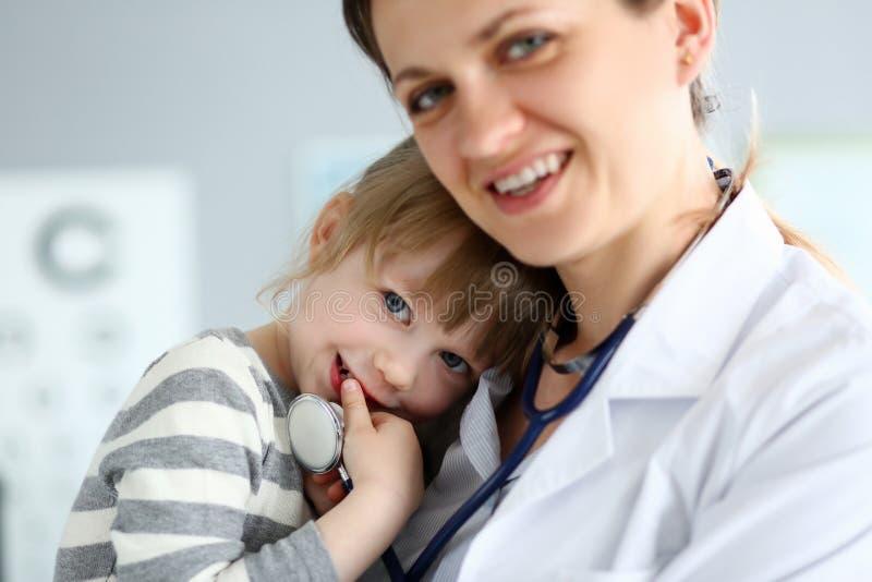 Παιδιατρικός γιατρός που κρατά και που αγκαλιάζει λίγο χαριτωμένο ασθενή κοριτσιών στοκ εικόνα