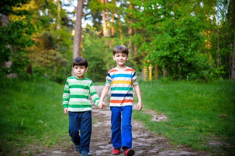 Παιδική ηλικία, πεζοπορία, οικογένεια, φιλία και έννοια ανθρώπων - δύο ευτυχή παιδιά που περπατούν κατά μήκος της δασικής πορείας στοκ εικόνες με δικαίωμα ελεύθερης χρήσης