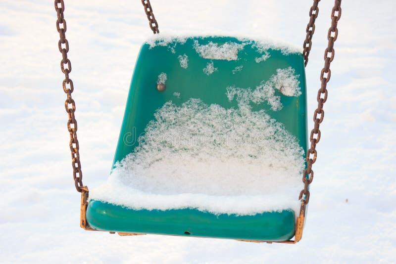 Παιδική χαρά παιδιών το χειμώνα, την ταλάντευση και τα ιπποδρόμια κάτω από το χιόνι μια ηλιόλουστη ημέρα κανένας άνθρωπος, κενή π στοκ φωτογραφία με δικαίωμα ελεύθερης χρήσης