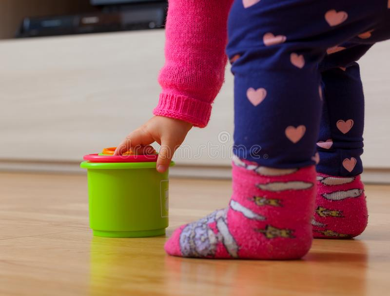 Παιχνίδια κοριτσάκι μικρών παιδιών με τα χρωματισμένα φλυτζάνια στοκ εικόνα με δικαίωμα ελεύθερης χρήσης