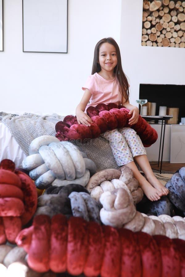 Παιχνίδια κοριτσιών παιδιών μεταξύ των ασυνήθιστων μαξιλαριών στις π στοκ φωτογραφία