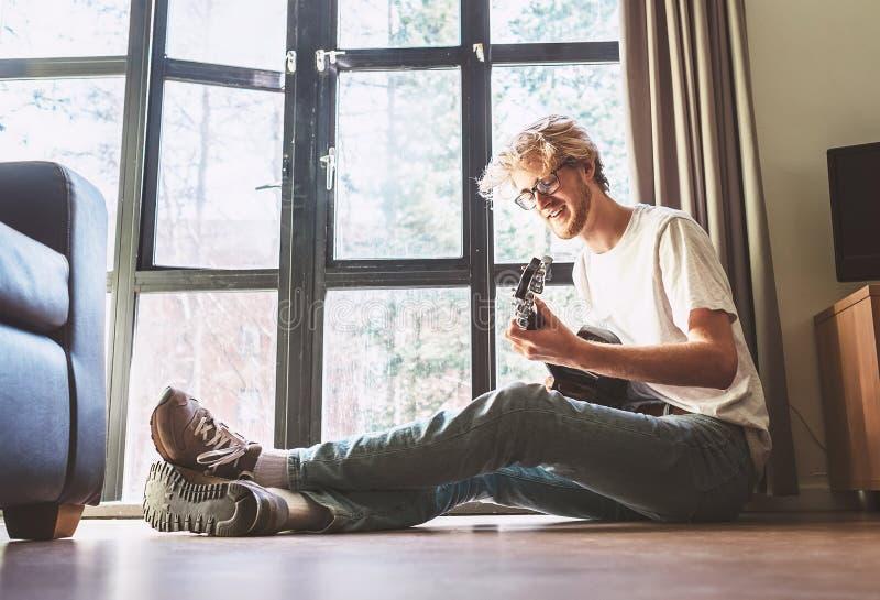 Παιχνίδια νεαρών άνδρων στη συνεδρίαση κιθάρων στο πάτωμα στο καθιστικό στοκ εικόνα με δικαίωμα ελεύθερης χρήσης